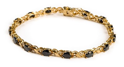 Lot 3-Bracelet. A 9ct gold ladies bracelet set with 15 sapphires and 30 diamond chippings