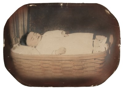 Lot 24-Post-mortem of a child. A full-length portrait of a young child lying in a wicker basket, c. 1880s