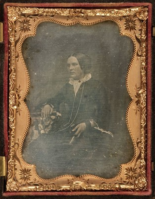 Lot 30 - Daguerreotypes. A one-quarter plate daguerreotype of a seated young woman holding a book, circa 1860